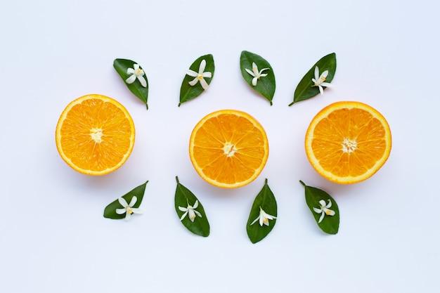 Teneur élevée en vitamine c. agrumes orange frais avec feuilles et fleurs blanches