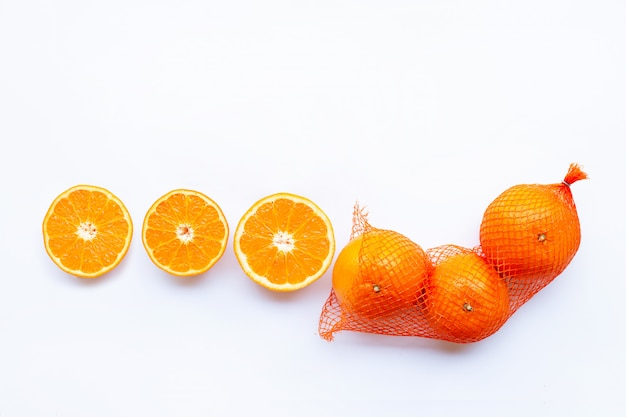 Teneur élevée en vitamine c. orange dans un sac en filet avec la moitié mûre d'orange sur fond blanc.