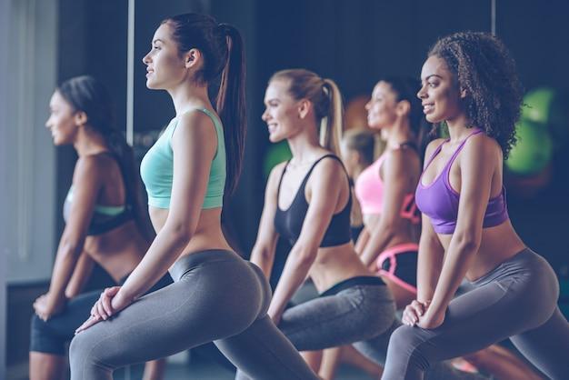 Tenez bon les filles ! vue latérale de belles jeunes femmes avec des corps parfaits en vêtements de sport faisant de l'exercice avec le sourire au gymnase