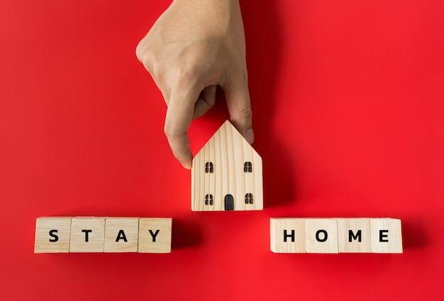Tenez la main sur une maison modèle en bois et restez des blocs de maison
