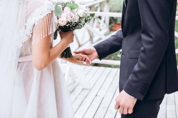 Tenez-moi et ne lâchez jamais. heureux jeunes mariés se tiennent la main