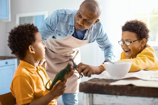 Tenez-vous bien. aimer le jeune père essayant de calmer ses petits fils pendant qu'ils s'amusent et jouent avec des jouets pendant le petit-déjeuner