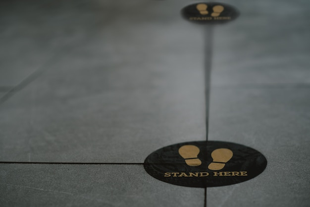 Tenez-vous ici pied signe ou symbole sur le sol dans un café