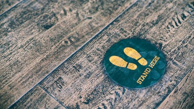 Tenez-vous ici signe de pied ou symbole sur le sol