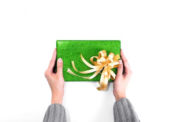 Tenir le cadeau de noël avec du papier d'emballage à paillettes vertes et un ruban d'or