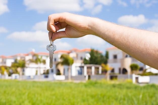 Tenir les clés de la maison sur un porte-clés en forme de maison en gros plan devant un nouveau concept de maison de l'immobilier