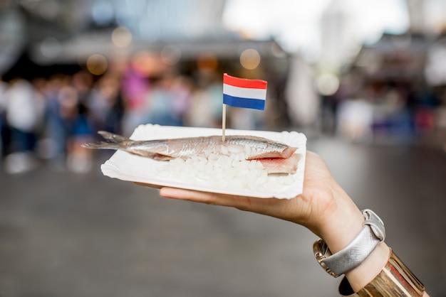 Tenir le hareng avec des oignons snack hollandais traditionnel