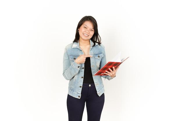 Tenir le livre de la belle femme asiatique portant une veste en jean et une chemise noire isolée sur blanc