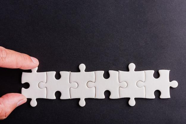 Tenir à la main les dernières pièces du jeu de puzzle en papier blanc de six pièces, dernières pièces pour résoudre le problème