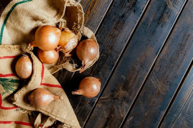 Tenir à la main un sac en tissu d'oignon frais isolé sur une surface en bois b
