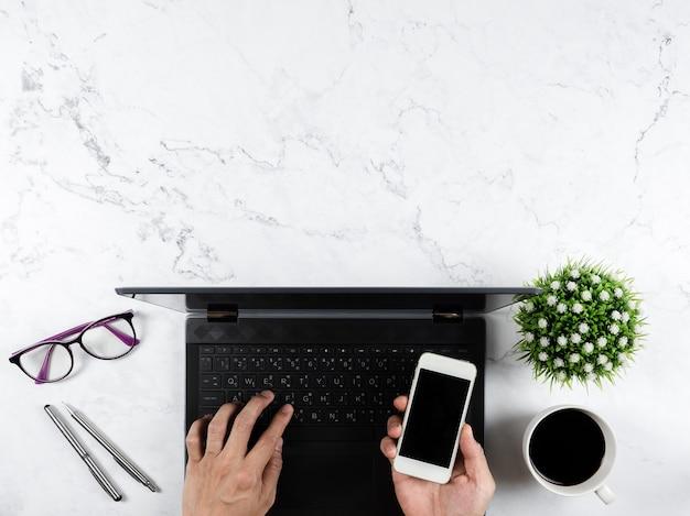 Tenir à la main un smartphone sur un ordinateur portable à clavier avec des lunettes, un stylo argenté, une tasse à café, un vase à fleurs sur une table en marbre