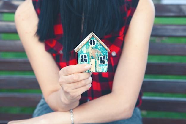 Tenir une maison à la main en étant assis sur un banc