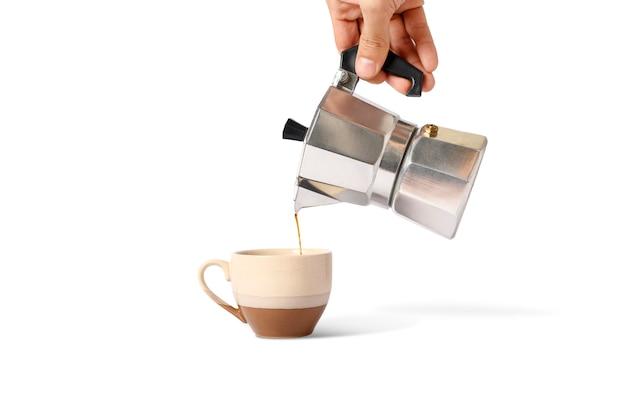 Tenir le pot moka avec verser du café sur une tasse isolée.