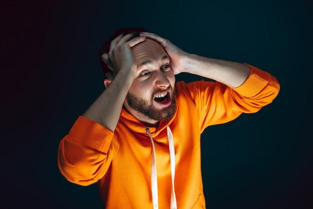 Tenir la tête. portrait d'un homme caucasien fou effrayé et choqué isolé sur fond sombre. copyspace pour l'annonce. expression faciale lumineuse, concept d'émotions humaines. regarder l'horreur à la télévision, au cinéma.