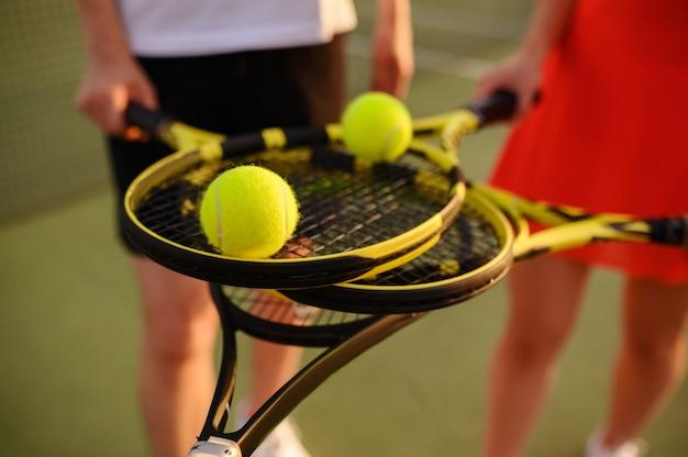 Tennis en double mixte, joueurs avec raquettes et balles