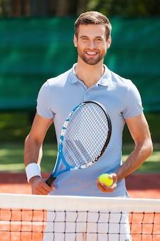 Le tennis, c'est ma vie ! heureux jeune homme en polo tenant une raquette de tennis et une balle en se tenant debout sur un court de tennis