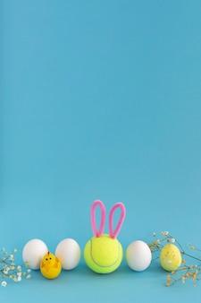 Tennis de pâques, composition verticale avec espace copie sur le dessus. balle de tennis souriante avec oreilles de lapin et oeufs de pâques sur fond bleu.