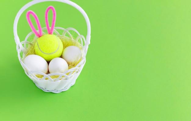 Tennis de pâques. dans un panier blanc oeufs de pâques et balle de tennis avec des oreilles de lapin sur fond vert avec espace de copie.