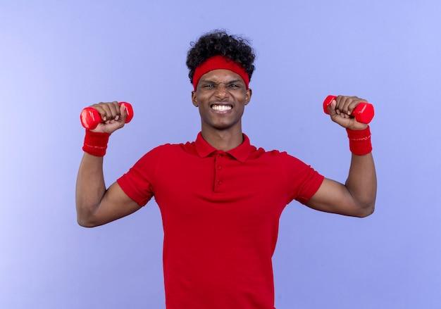 Tense jeune homme sportif afro-américain portant bandeau et bracelet soulevant des haltères isolé sur mur bleu