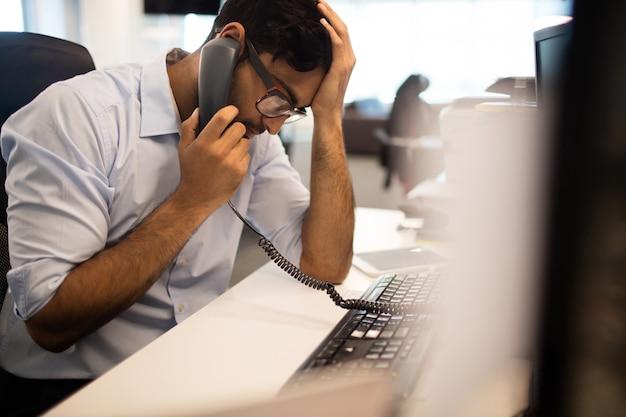 Tensed businessman parler sur ligne fixe au bureau