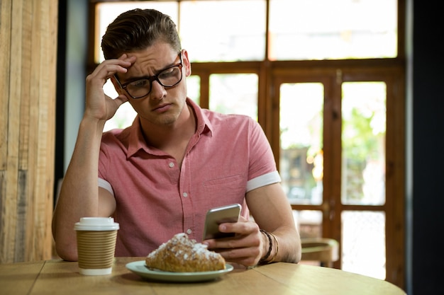 Tensed young man using smart phone at table in coffee shop