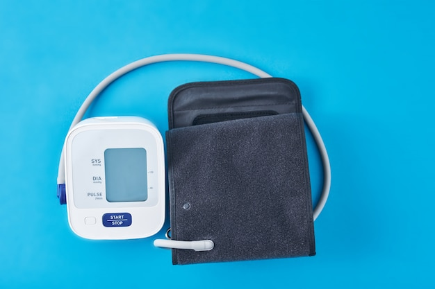 Tensiomètre numérique sur fond bleu, gros plan. helathcare et concept médical