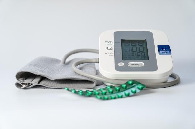 Tensiomètre pour prendre la tension artérielle et des pilules pour l'abaisser.