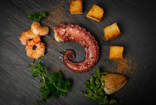 Tentacule de poulpe grillé sur plaque de pierre noire servi avec des crevettes