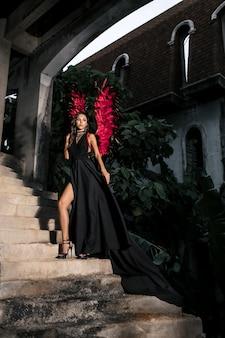 Tentatrice. femme sur le visage passionné joue le jeu de rôle. fille démon sexy en robe noire avec des ailes rouges, diable plein de désir debout dans les escaliers. halloween