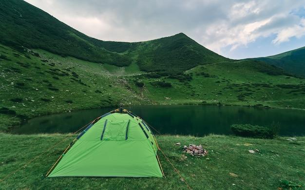Une tente au bord du lac au pied de montagnes verdoyantes couvertes de buissons et d'herbe par temps nuageux d'été. tourisme, repos, loisirs. paysage de montagne.