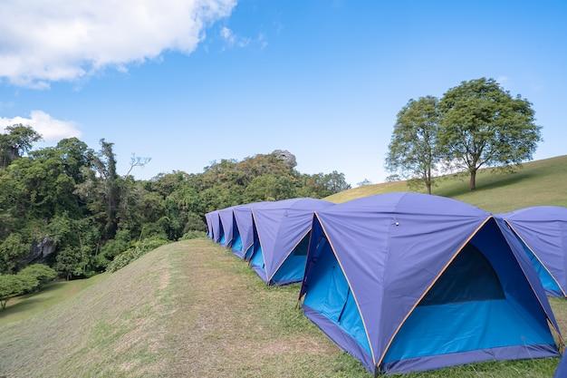 Tente bleue bordée sur le fond de la pelouse montagnes et ciel à phu soi dao, nan en thaïlande.