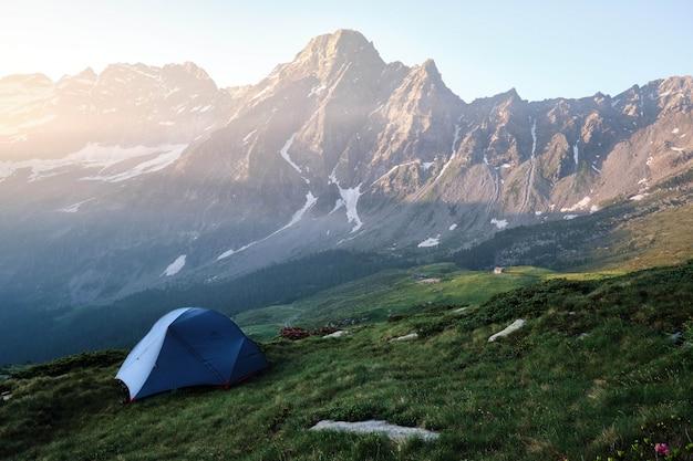 Tente bleue sur une colline herbeuse avec montagnes et ciel clair