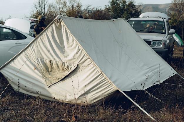 Tente de camping et deux voitures sur un pré
