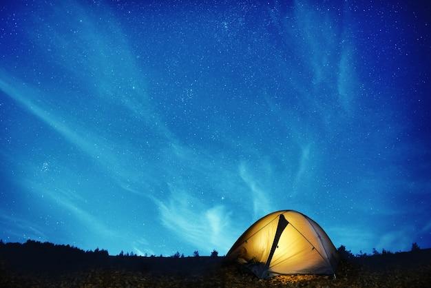 Tente de camping jaune illuminée sous les étoiles la nuit