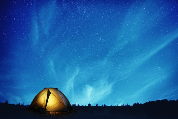 Tente de camping jaune illuminée sous de nombreuses étoiles et la nuit