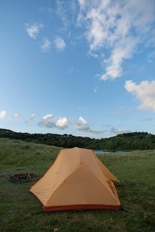 Tente de camping orange au bord du lac dans un paysage magnifique