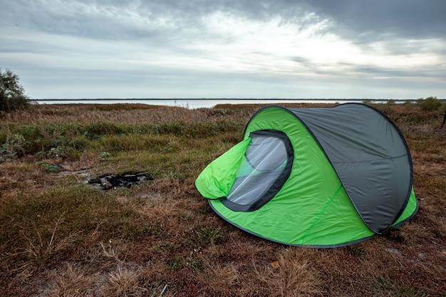 Tente de camping verte en arrière-plan de la nature et du lac. voyages, tourisme, camping.