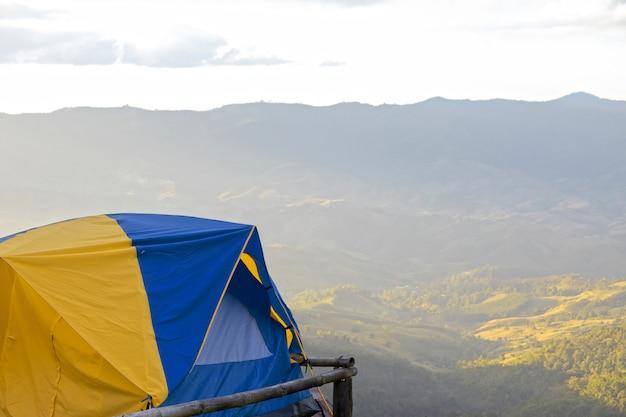 Une tente de couleur jaune et bleue au sommet des collines.