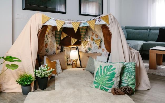 Tente faite maison avec trois chaises et draps dans le salon