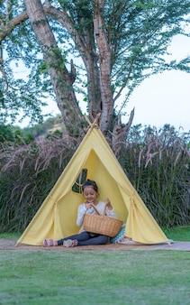 Tente jaune avec une petite fille mignonne à l'intérieur dans la nature
