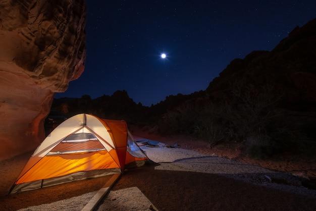 Tente orange campant la nuit avec la lune et les étoiles dans le ciel