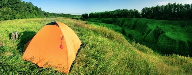 Tente orange sur une colline verte au-dessus d'un ravin
