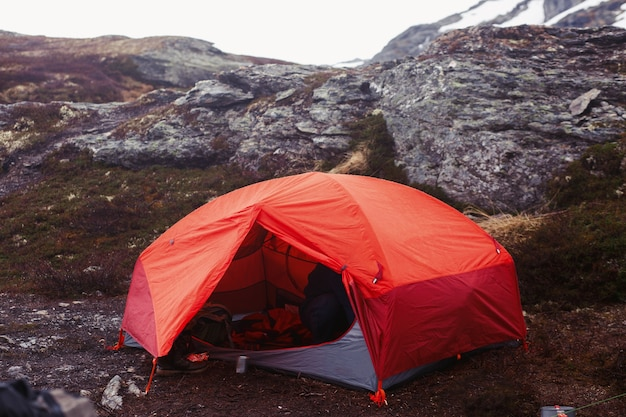 Une tente rouge se tient sur le sol quelque part dans les montagnes