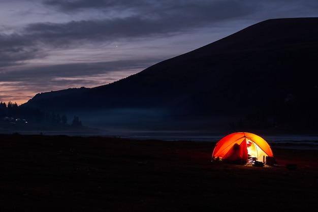 Tente rougeoyante sous un ciel nocturne plein d'étoiles.