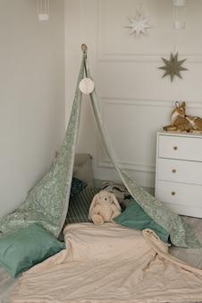 Tente tente pour enfants avec oreillers et un lapin en peluche dans la chambre pour les petits enfants