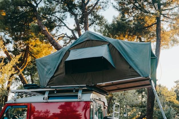 Tente de toit pour camper sur la galerie de toit d'une voiture suv tout-terrain dans un parc naturel