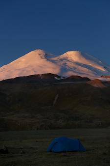 Tente touristique sur le fond des sommets enneigés du mont elbrouz en russie