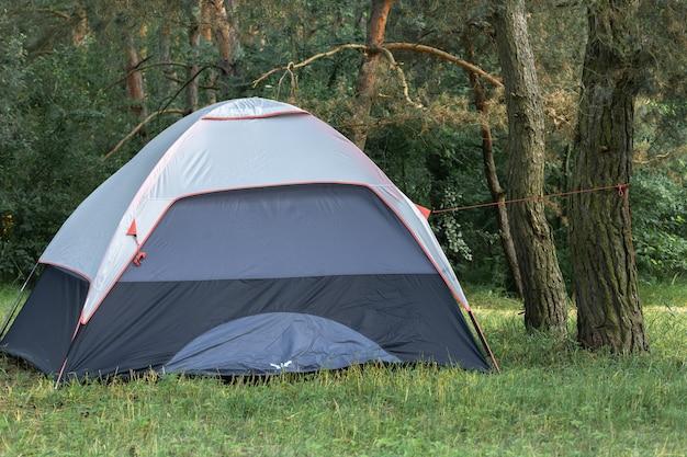 Une tente touristique grise se dresse dans la forêt à côté d'un conifère.