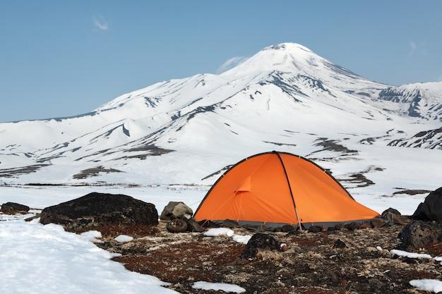 Tente touristique orange debout sur un pré entouré de neige sur fond de cône volcanique pittoresque