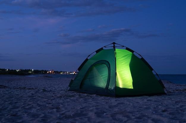 La tente verte brille de l'intérieur la nuit